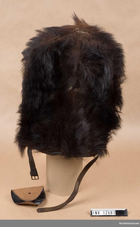 C I.Av björnskinn.   Läderplatta utan emblem har lossnat från mössan.