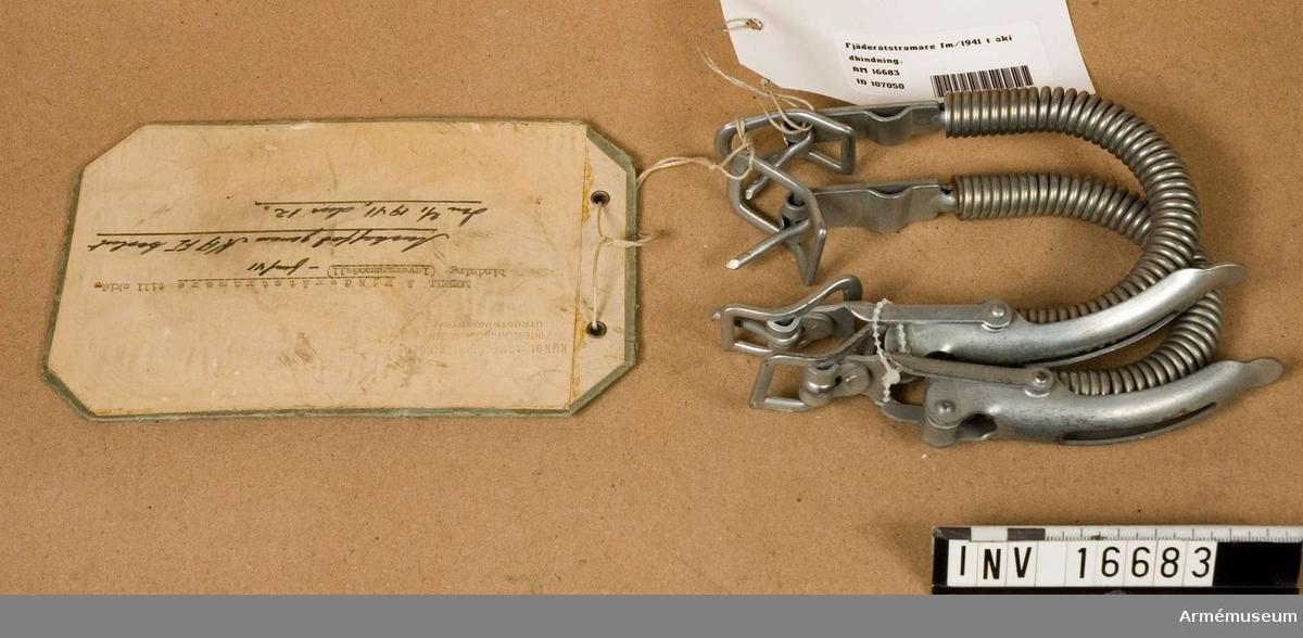 """Leveransmodell. Av stål och består av en krökt fjäder med excenterhandtag och två spännen för sidstropp med krok. Märkt """"Pat.104214"""". Modellapp: """"Kungl Arméförvaltningens intendenturavdelningen utrustningsbyrån. Modell av Fjäderåtstramare till skidbindning (leveransmodell) -fm/41."""