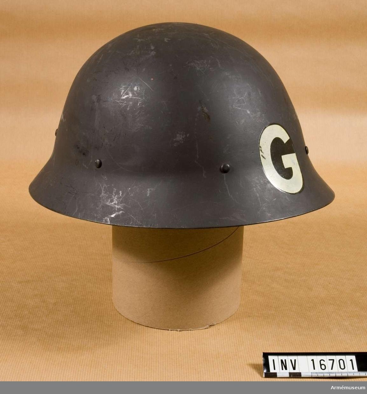 """Målad stålhjälm, slät och utan fals runt brättet. Sex nitar runt kullen. Har inredning och hakrem. Mitt fram märkt: """"G"""", 60 mm högt. Hjälmen är moderniserad 1939."""