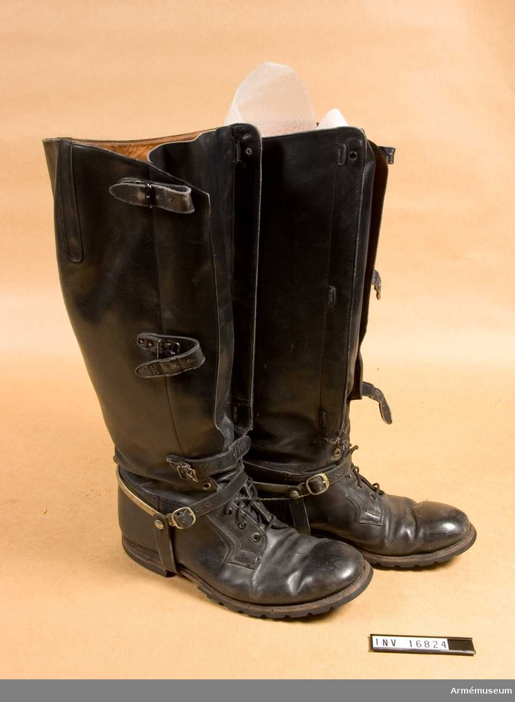 Tillverkade av A/B Örebro skofabrik 1950. Storlek 44. Av svart läder och fodrade med ljusbrunt skinn. Lädersula som har en vulkaniserad gummisula och klack påsatt. Snörning på skon och framtill på benet spänns stöveln med tre läderremmar. Spännsporrar med läderremmar på skon.