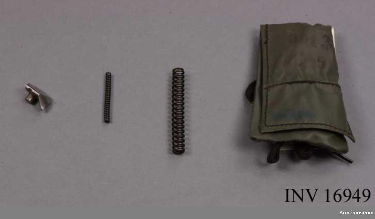 """Kaliber 6,5 mm. Påse av plastväv. Märkt """"0013 6,5"""". Består av: 1 reservdelspåse, 1 utdragare, 1 matarfjäder, 1 tändstiftsfjäder."""