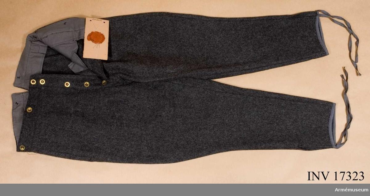 Grupp C I. Byxor av mörkgrått kläde - ridbyxor modell med 2,5 cm bred grå lampass av kläde. Byxorna har fyra fickor (2 på sidan, 1 liten för klocka, 1 på baksidan), sprund med fem svarta knappar, hyska och hake. Sex svarta knappar för hängslen. På baksidan spänntamp av kläde. Foder av svart satintyg. Fållarna försedda med bomullsband (hällor). På byxornas baksida finns en besäts av kläde och byxbenen på insidan besatta med mjukt grått kläde.