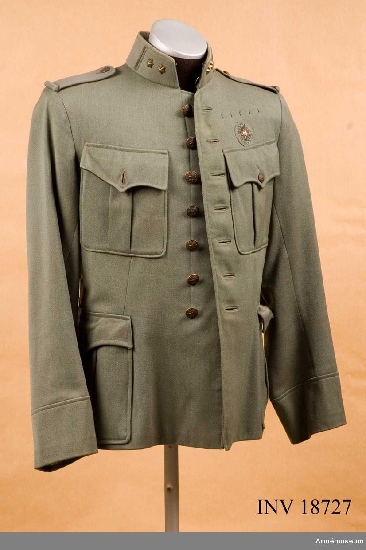 """Grupp C I. Ur uniform för överstelöjtnant vid Koninklijke-Neder- landscke-Cavalerie, Holland. Av grått diagonaltyg, enradig med 7 knappar. Åtsittande. På bröstet, på vänstra sidan, en 4-uddig stjärna med lejon i mitten, allt påsytt på en rund tygbit. I ryggsömmarna finns två vapenprydda krokar till bältet och på sidorna två krokar för livremmen. Axelklaffar av samma tyg, b:50 mm, l:110 mm, fastsydda vid ärmsömmarna och fästade vid rocken med knappar (liten modell). Två påsydda sidofickor och 2 bröstfickor. Alla fickorna äro försedda med vertikala motveck. Ficklock med avrundade hörn i mitten, utdragna till en spets och försedda med en vapenprydd knapp av mindre modell. Foder av mörkgrått bomullstyg med inre sidoficka. Knappar av brons med statsvapnets krönta lejon, på bröstet  vid knäppningen 7 st, d:20 mm och på axlarna 2 st d:15 mm. Krage upprättstående med raka vinklar. På kragen finns två stjärnor balk med brodering tvärsöver kragen (Kännetecken för stabsofficer med överstelöjtnants grad). Foder av grått tyg med två hyskor och hakar. Ärmuppslag av  samma tyg 9 cm höga, rakskurna. LITT  Handbuch der Uniformkunde. Prof. Richard Knötel. Hamburg 1937. Sida 257, """"Die graue Felduniform, ihre waffen Rangab- zeichen"""". År 1912 infördes i holländska arméen fältgrå uniform.  Fullständig beskrivning för vapenrock med 7 knappar och upprättstående krage. Sid 257 efter tabell för olika truppslag. För infanteri passpoal för krage och ärmuppslag blå (kännetecknande färg för infanteri).Enl W Granberg 1954."""