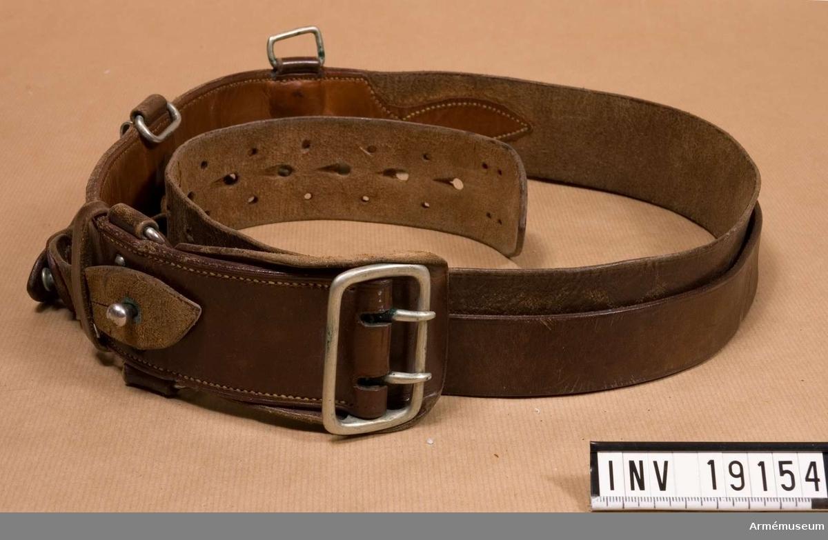 Samhörande nr är: 19145-60, rockar, byxor, mössor m m. Av brunt läder med metallspänne och övriga belag av metall. Gåva av M Kinmanson, Tobakspinnarg 5, 117 36  Stockholm.