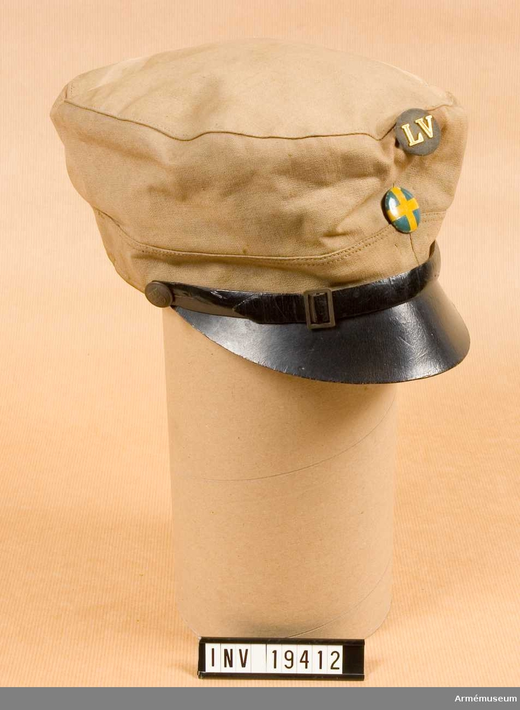Mössa m/1926 för landstormspojke vid luftvärnsavdelning.Svartlackerad mössrem och skärm. Framtill finns en knapp i textil för luftvärn och lanstormsmärke.