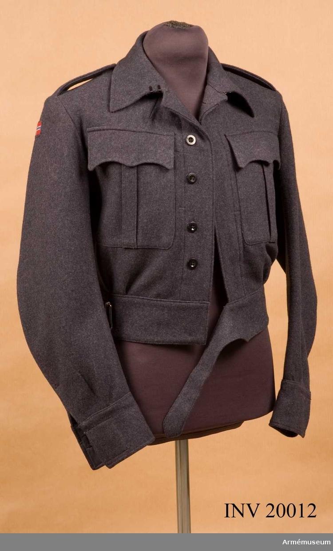 """Grupp C I. Ur uniform 1943 för manskap vid infanteriet i Norge. Blus (kort jacka) av blågrått kläde, enrandig med 5 knappar. Längs nedre kanten en 7 cm bred remsa av samma kläde med dito bälte och spännen. Axelklaffar av samma kläde, l:120 mm, b:50 mm. Fastsydda vid ärmsömmarna och fästade vid vapenrocken med benknappar. Två bröstfickor med inre knapphål och knappar i de med verti- kala motveck utrustade locken. Foder saknas. På klädets innersida finns vid knäppningen fastsydda remsor och två innerfickor av mörktgrått tyg. Knappar: På bröstet 5 st, på locken 2 st, vid ärmuppslagen 2 st. Alla är svarta benknappar. Krage, liggande, med två hyskor och hakar. Ärmuppslagen rakskurna med inskärning och innerknapp. På högra ärmens övre del finns fastsydd tygbit med norska nationalflaggan. På vänstra ärmens övre del finns fastsydd en svart tygbit med ordet """"Norway"""" broderat i vitt."""