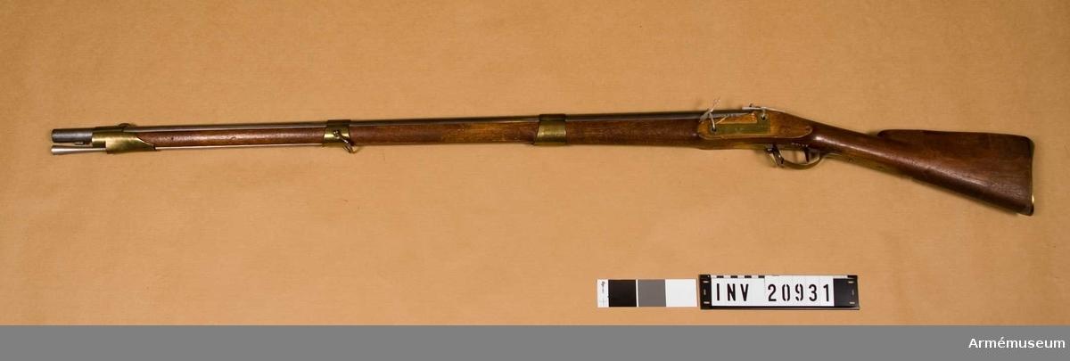 Grupp E II b 1815 års tredje modell. Gevärets vikt: 4,81 kg. Kulans vikt: 30,6 gr. Krutladdningens vikt 9,98 gr. Utgångshastighet 1285 fot=382 m. Med undantag av det höga siktet samt att färpannan är av järn i stället för av brons överenstämmer vapnet helt med  AM 1975:23546. På pipans översida står FOS, ASvW, IH  samt krönt NT.  På undersidan är IH inslaget två gånger och dessutom står där 2,p,352 och 1836. På pipans bakplan otydligt N,F,Y, och LO. På svansskruvstjärten är inslaget 324 och 352.  Det på 1815 års modell brukliga siktet har här enligt 1838 års förordning utbytts mot ett med omkring 9 mm lång, bakåtvänd fot försett högt ståndsikte, som är fastlött framtill på svansskruvstjärtens översida.  Siktklaffen har smal siktskåra. Låsets samtliga skruvar samt överläppen och läppskruven är blånade. På låsbleckets utsida finns ett krönt NT samt numret 324, men på insidan IG, en otydlig kronstämpel och 1836.   Flertalet låsdelar är märkta med siffran 2. Stocken är av björk och brunbetsad. På stockens vänstra sida bakom sidblecket är inslaget 324, 1836 och IH.  I urtagningen för varbygelns bakre arm är inslaget SB. På sidbleckets, på bandens samt på bakplåtens spets sitter en  liten kronstämpel.  På laddstockens stötskiva finns en kron- stämpel och ett H.  På äldre gevär fastlöddes de nya siktena, men vid nytillverkning skulle de göras i ett stycke med svansskruv- stjärten.  Tillverkningsnummer 324  Samhörande nr är AM.20931-2