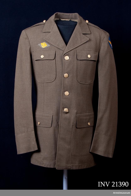 """Grupp C I. Av grönt kakikläde. Enradig med 4 knappar. Stor modell. Nedanför midjan en slits, l:310 mm. Axelklaffar av samma gröna tyg, l:160 mm, b:50 mm, fastsydda i ärmsömmen och fästade vid rocken med en knapp. Bröstmärke för flyg är fastsytt på bröstet; Örn och ring broderade av gult silke på en kakifärgad tygbit. Fickor; på framsidan två bröstfickor och två störe sidofickor, alla täckta med fyrkantiga lock som har en knapp. Foder av kakifärgat bomullstyg. På fodret, i ryggen, finns påskrift """"G-0265"""". På H sidoficka står """"Gillespie WM, 0265"""". Knappar av gul metall med amerikanskt vapen, d:22 mm, 4 st på bröstet med d:15 mm; 2 st på axelklaffarna, 4 st på fickor. Kragen öppen och liggande. Ärmmärke, runt, för flygstridskrafter; två gula vingar och vit stjärna i mitten på blå botten.  LITT  Handbuch der Uniformkunde. Prof R. Knötel. Hamburg 1937. Sida 400. Under Spanska kriget år 1898 infördes i amerikanska armén kakifärgade uniformer. Vapenrocken har fem knappar på bröstet med bröst och sidofickor, År 1926 förändrades fältuniformen - knapparna blev av matt guld och rocken fick civil- snitt. The officers guide. The military service publishing company. Harrisburg, Pennsylvania 1943, sida 145. Bilaga, Olika militärmärken i färger; Sid 3. Fjärde i rad. """"Army Air Force"""" luftstridskrafterna. Amerikanska uniformer ur """"Life"""" 1941-05-19 s. 4. Andra bilden 6. Olika armémärken: vapenemblem för knappar """"Capemblem""""."""