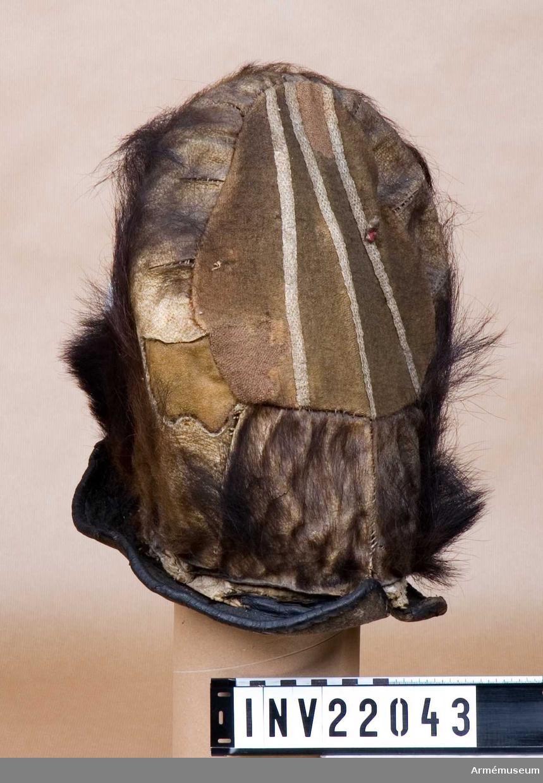 Grupp C I. Grenadjärmössa tillverkad av kartong med björnskinn spännt över på framsidan, medan baksidan är av rött ylle. Formen hålls uppe med hjälp av rottingpinnar. En filthatt med brätte är monterad innuti mössan. Runt mössans nederkant, ovanför brättet har det suttit en mässingskordong som nu är borta. På baksidan sitter spår av en röd och vit banderoll.