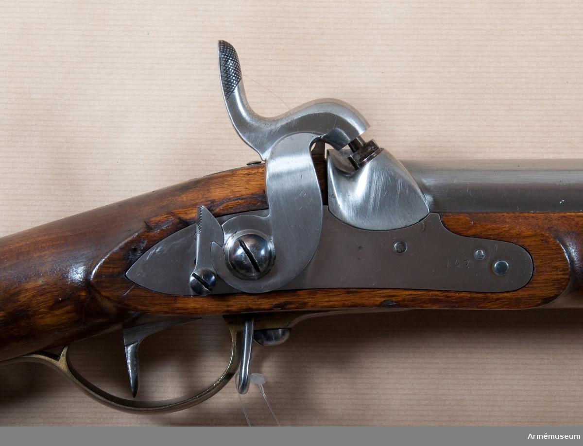 Grupp E II.  Geväret är förändrat från ett flintlåsgevär m/1815, se AM 1932:4208-4209, som enligt 1838 års förordning försattes med högre sikte AM 1932:4210. Förändringen berör endast antändningssättet.Nominalkaliber 18,5 mm. Verklig kaliber 18,2 mm. Loppets relativa längd 56 kaliber. Utgångshastighet 377 m/sek =1270 fot. Kulvikt 30,8 gram. Kuldiameter 17,5 mm. Krutladdningens vikt 8,38 gram.  På PIPANS H platt på fänghålets plats har en med eldskärm försedd snäcka fastlötts med mässing. I snäckan är knallhattstappen inskruvad. På pipans översida står krönt C, några otydliga bokstäver och 26. På V platten är inslaget 147 och längre ned på V sidan siffrorna 3 samt 5. På undersidan står LT, 2, NW och P. På svansskruvsstjärtens undersida är inslaget 147.  På LÅSET har eldstålet, eldstålsfjädern och fängpannan tagits bort. Hålet för eldstålsskruvens skruv är igenfyllda. På fängpannans plats finns urtagning för pipans snäcka. Varhaken är upptill på baksidan krusad. Hanen är nygjord vid förändringen, kraftig samt har platt och hals med rektangulär genomskärning. I slaghuvudet finns en 7 mm djup urtagning, vars botten bildar slagytan. Tumgreppet är upptill på framsidan krusat. På bleckets utsida finns krönt C och 147, på insidan ÅG och 1832. I halvspänn står hanen ganska högt, men i hakspänn står hanens slagyta blott omkr 3 mm över knallhattstappen.  På KOLVENS högra sida finns rester av ett rött lacksigill. På bakplåtens spets står 147. På insidan av sidblecket, nedre bandet och näsbandet är inslaget ett B, men på insidan av mellanbandet ett par otydliga bokstäver, möjligen IG.  På LADDSTOCKEN är smaländens gängade parti avbrutet. På stötskivan står ett L.Geväret är ursprungligen ett i Karl Gustafs stads gevärsfaktori 1832 tillverkat flinlåsgevär m/1815, som senare ändrats till slaglås enligt 1845 års förändringsmodell. På detta gevär synes ändringen ha gjorts i Karl Gustafs stads gevärsfaktori, men vanligen skedde den, liksom övriga reparationer, vid något av gevärsförrå