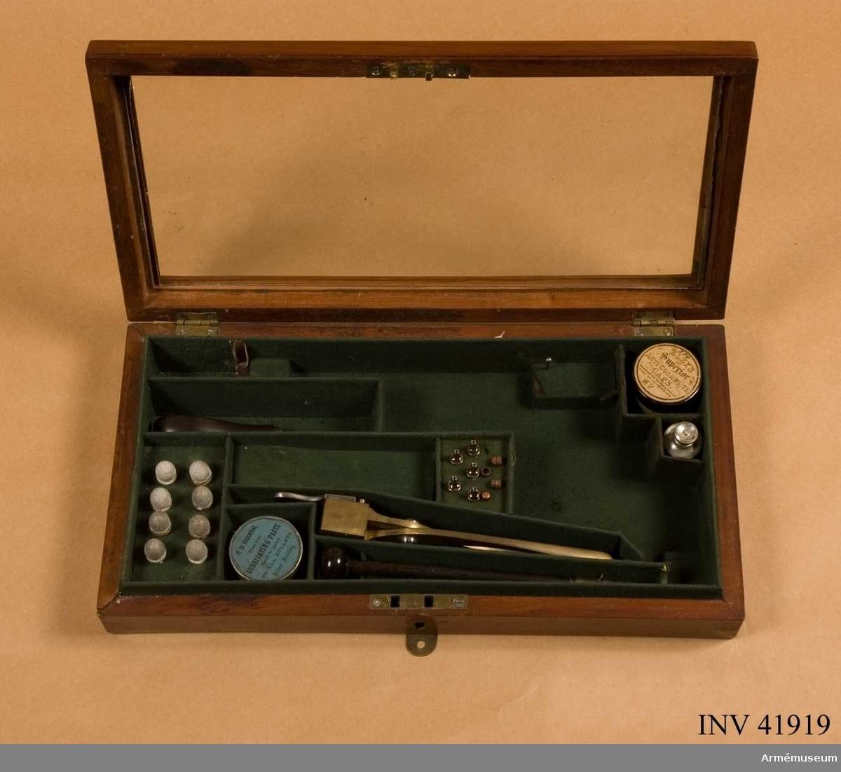 """Grupp E III. Låda med glaslock.Lådan innehåller: en kultång av mässing märkt på skänklarna med """"48"""" och """"WD"""", en """"smörjdosa"""" av aluminium, fem stycken tändhattsnipplar, fyra stycken tändhattar av koppar troligen skarpa, en läskstång av trä med mässingsända, en tändhattsnippelnyckel med rensnål i handtaget, åtta stycken blykulor (korroderade), en burk i lackerad plåt med texten: """"250 Eleys superior anti corrosive caps. warraned neihter to miss fire or fly to pieces. No. Made expressly for Webbleys patent safty pistols & revolvers"""", en plåtburk (tom) med texten: """"It is essential that this Lubricating paste should be applied to all bullets before loadning."""" Det verkar som om lådan har varit utställd tidigare då man försökt fästa innehållet med ståltråd och limmat och spikat (!) fast plåtburkarna. Glaset i locket passar dåligt och är mycket illa tillskuret, ditsatt efteråt måhända?"""