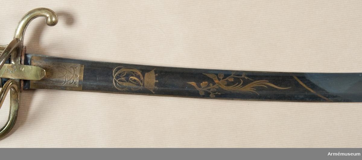 Grupp D II På klingan förekommer kronprins Karl Johans namnchiffer. Fästet är förgylld mässing och har två spänger. Klingan är böjd, till sin större eneggad och skålslipad. Upptill  blåanlöpt med inläggningar av guld.   Samhörande nummer är AM.43976-7