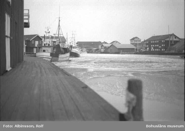 """Enligt fotografens noteringar: """"Parti av Smögenbryggan åt öster. Fiskebåten Sonja ligger vid kaj på andra sidan. I centrum en låg byggnad, detta är gamla fiskeauktionbyggnaden när den låg på Holmen.""""  Fototid: 1996 den 12 januari."""