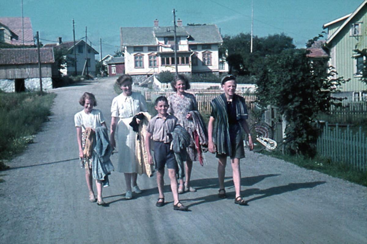 """Enligt noteringar: 70 st. ramade dia. + 5 st. burkar med oramade dia. Båtar, Varv, Hav, Människor.  Film nr. 123  Sörgård Öckerö. På bilden från vänster* 2 sommargäster, pojken i mitten är Gunnar Utbult och hans syster Gunnel Utbult (barn till riksdagsman Olof Johansson) pojken t.h. badgäst. Vita huset, """"Källarvinden"""" , längst fram t.v. där gaveln syns, är Ludvig Anderssons som revs när vägen i Sörgård rätades ut. Stora vita huset med veranda är John Olofssons, t.h. skymtar Valfrid Hanssons hus."""