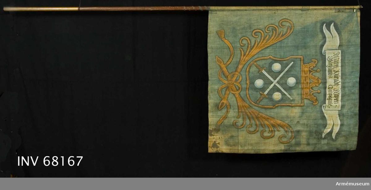 Duk: Tillverkad av enkel blå linnelärft. Två vertikala våder hopsydda med fällsöm i mitten. Stad i vertikala ytterkanten. Fållen i över- och underkanten lagd åt dukens insida. Fäst med en rad sexuddiga tennlickor på blått band. Har ursprungligen fortsatt 250 mm ned på stången.  Dekor: Målad lika på båda sidor i mitten i gult en med öppen krona krönt sköld, nedtill innefattad av två korsade och med långa tofsprydda band. Hopknutna palmkvistar. I skölden två korsade svärd med vita klingor och gula fästen, följda av fyra i vinklarna ställda vita kulor. Text på båda sidor om det vita inskriptionsbandet.  Stång: Tillverkad av trä, brunmålad. Mässingsförlängning. Saknar holk och spets.