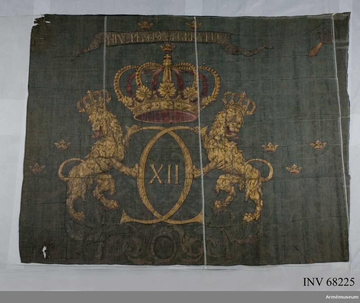 """Duk: Tillverkad av tre våder enkel blå sidendamast, sammansydd horisontellt. Mönster: vridna blad.  Dekor:  Målad lika på båda sidor, Karl XII:s namnchiffer, dubbelt C varinom XII, allt i guld, jämte en krönande, gyllene med rött även på byglarna innerfodrad stor sluten krona uppburet av två med slutna kronor krönta, ensvansade, utåtseende lejon i guld med röda tungor. Stående på ett postament i silver ett med luftigt lövformade voluter.  Över och under och på sidorna om chiffret """"tre kronor"""" i guld, på högra kortsidan (från dukens insida sett) fattas en av """"tre kronorna"""".  I hörnen granater i silver med inåtgående eldstråle i gult och rött. Endast inre granaten kvar (från dukens insida sett den vänstra). Över kronan text med guldbokstäver på inskriptionsband i silver."""