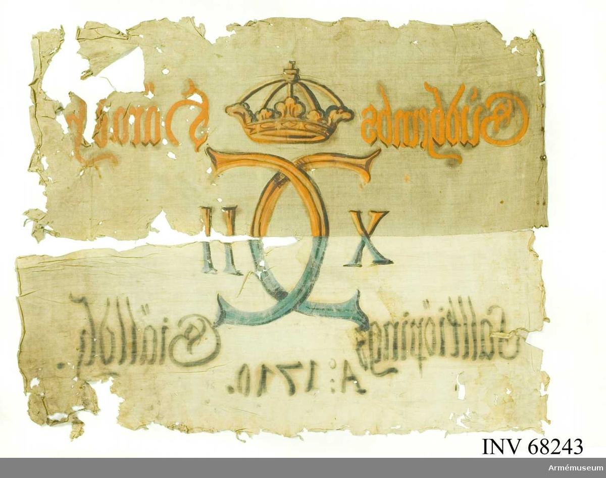 Duk: Tillverkad av vit linnelärft, sydd av två våder, horisontellt hopskarvade (med blå tråd). Målningen på dukens insida utfört på övre våden i ockra och brunt i nedre i blått ochsvart.  Dekor:  Carl XII, krönt spegelmonogram. Text på ömse sidor om monogrammet, upptill i gult och nedtill i svart.