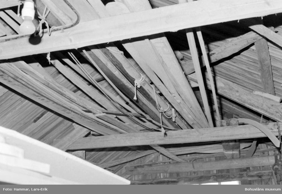 """Motivbeskrivning: """"F.d varv i Skredsvik, uppe vid taket syns bl.a mast och åror."""" Datum: 19800717"""