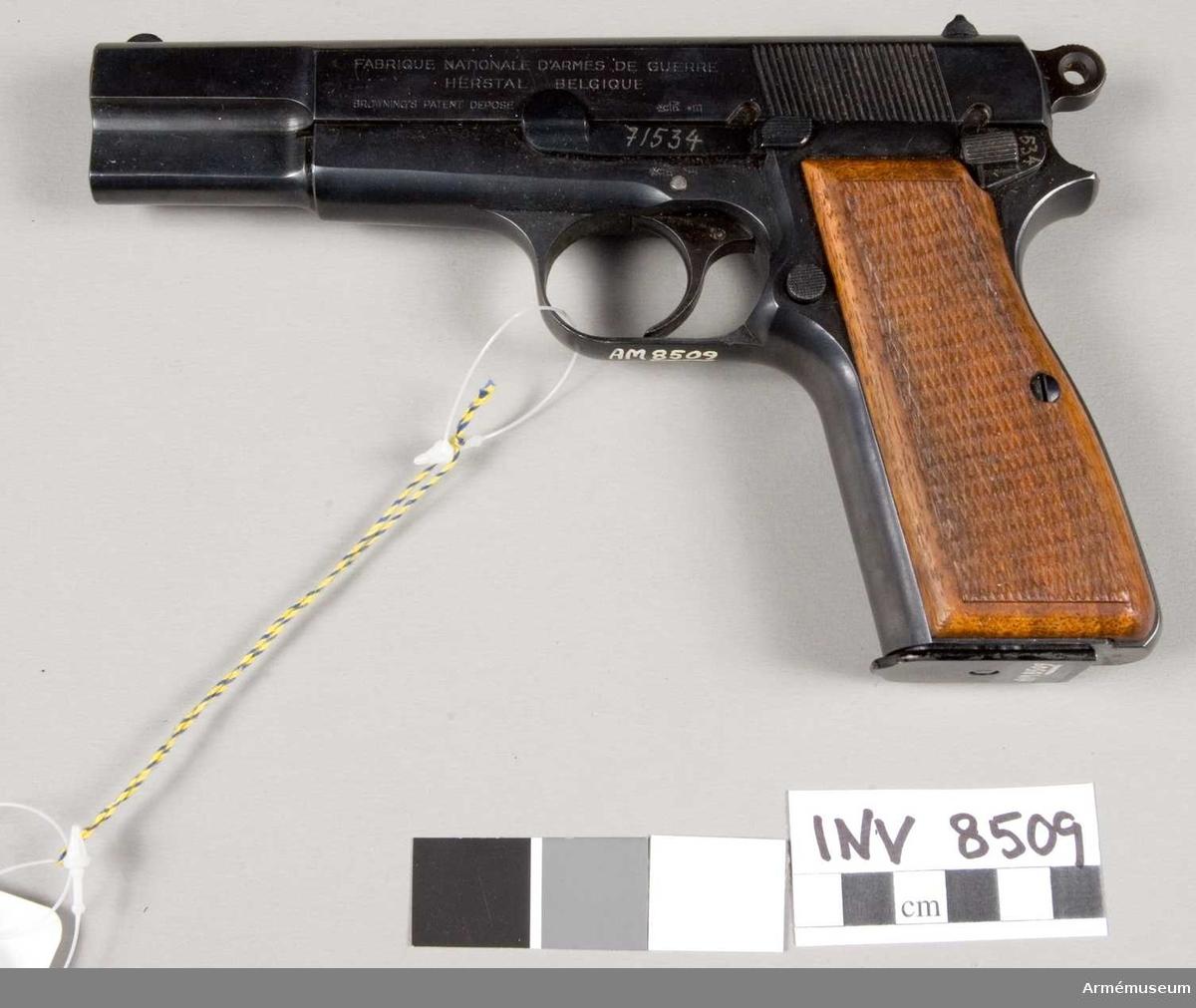 Tillverkningsnummer 71534. Tillverkare Fabrique Nationale D'armes de Guerre Herstal Belgique. Märkt ELG S P.V R (Browning's patent depose). Handgrepp av trä.Bestående av 1 st pistol, 2 st magasin, 1 st läskstång, 3 st patroner.