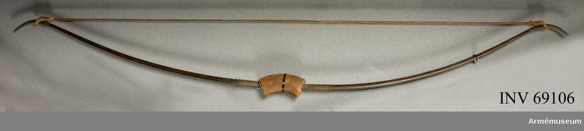 Båge av trä med metallskodda ändar. Med sträng av trä. Strängen fäst i bågen med snöre.