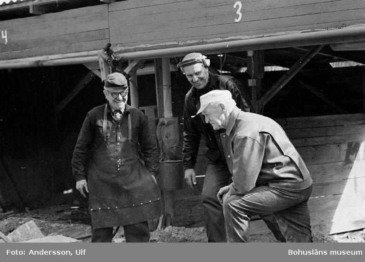 """Bohusläns samhälls- och näringsliv. 2. STENINDUSTRIN. Film: 15  Text som medföljde bilden: """"Diskussion kring kilning av 2 st grindstolpar. April 1977."""""""