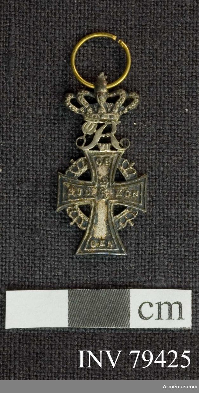 """Grupp M.  Åtsida: Ett silverkors med inskriptionen (i upphöjda bokstäver) lika fördelad på korsets armar. Högst upp R VII. Jämsides med ytterlinien löper en smal, upphöjd rand, i mitten """"C5"""" under kunglig krona.   Mellan korsets armar äro placerade kungliga kronor i en cirkel; ovanpå äversta armen """"R VIII"""" under kunglig krona.  Frånsidan: Samma utseende som åtsidan utom att """"R VII"""" står bakfram och inskriptionen är en annan.  På korsets översta arm """"F VI"""" under kunglig krona, på venstra armen: 1219, på högra armen 1671 och på den nedersta 1808, i korsets mitt: W under en krona.  Beskrivning: Carl Peyron."""