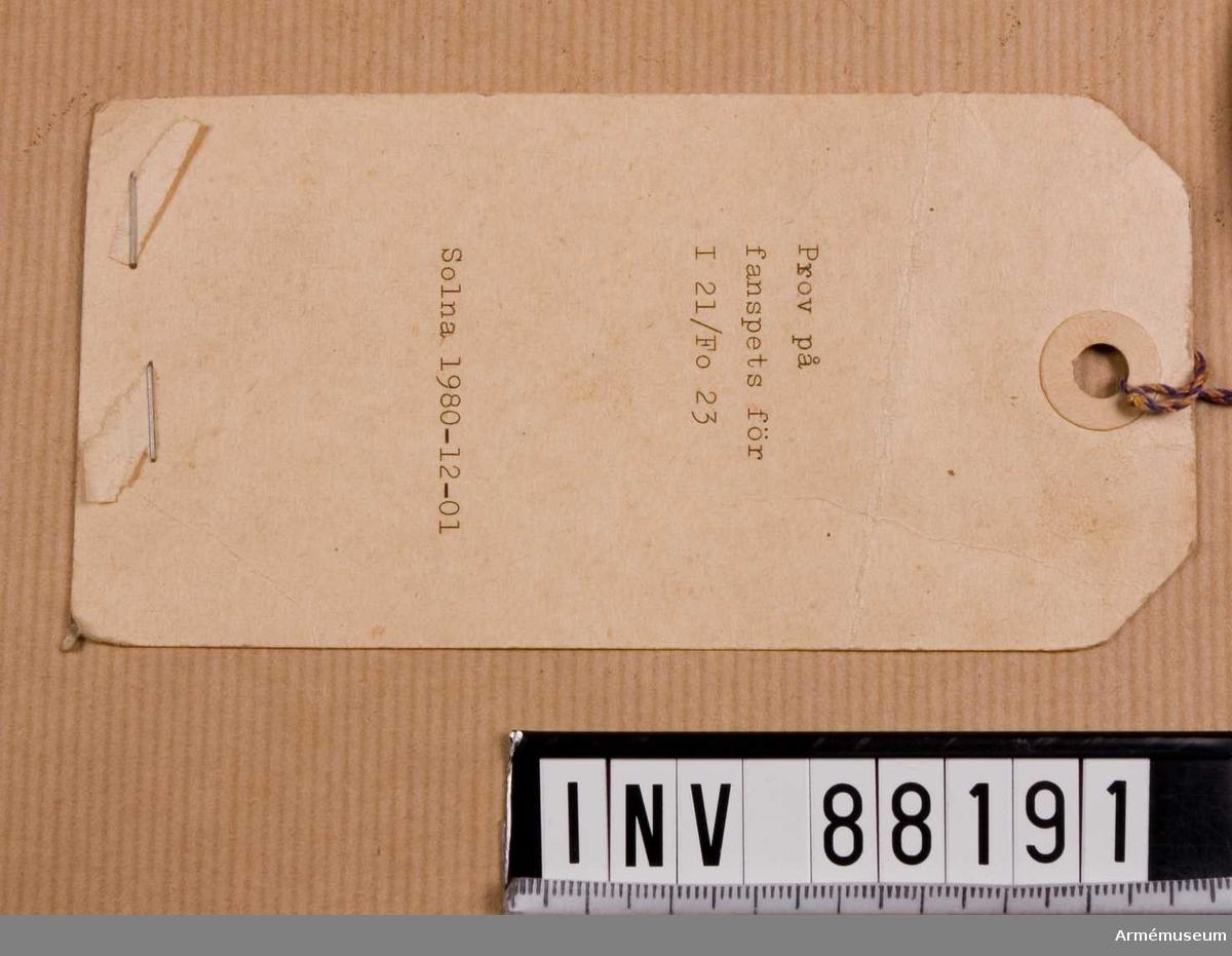Prov på fanspets för I 21/Fo 23. Solna 1980-12-01. Med Gustav VI Adolfs monogram. På etikett: Återsändes till FÖRSVARETS MATERIELVERK Huvudavdelningen för armémateriel Beklädnandsbyrån Box 1291 171 25 Solna