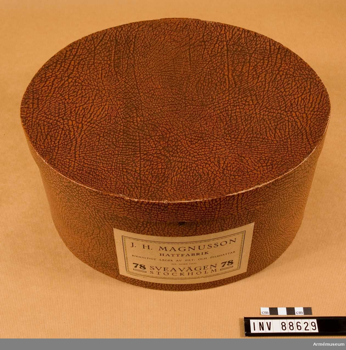 Hattask i papp med lädermönstrad utsida. Etikett med text: J.H. Magnussons hattfabrik. Sveavägen 78 Stockholm. I asken förvaras käppi AM. 88628.
