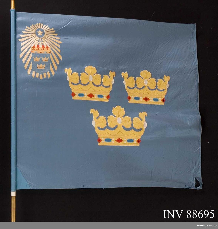 På ljusblå duk i mitten tre gula, öppna kronor. I övre inre hörnet en femuddig stjärna omgiven av ett gult stråknippe på vars nedre del lagts lilla riksvapnet. Vitmålad stång. Spets med Gustav VI Adolfs namnchiffer