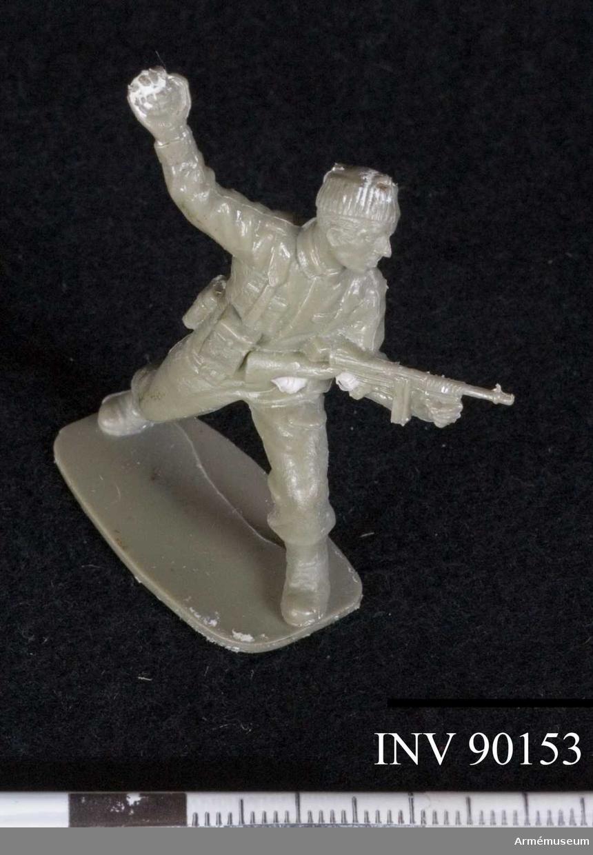 Soldaten håller den högra handen över sitt huvud såsom redo för ett kast av den handgranat han håller i ett fast grepp. I den vänstra handen håller han en Thomson m/1928. Klädd i en stickad mössa och med ett allvarligt ansiktsuttryck tar han ett steg framåt med den vänstra foten.