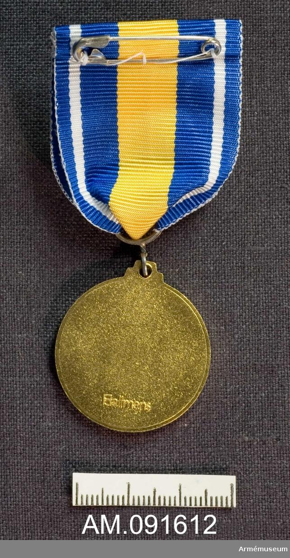 """Etui innehållande Medalj samt släpspänne. Byggnads- och reparationsberedskapens förtjänstmedalj, BRBGM. Märkt på framsidan med vapen och texten: """"BYGGNADS-OCH REPARATIONSBEREDSKAPEN BRB"""". Märkt på baksidan med firmanamn: """"Hallmans"""". Band i blått med en vit rand på vardera sidan och en gul rand på mitten."""