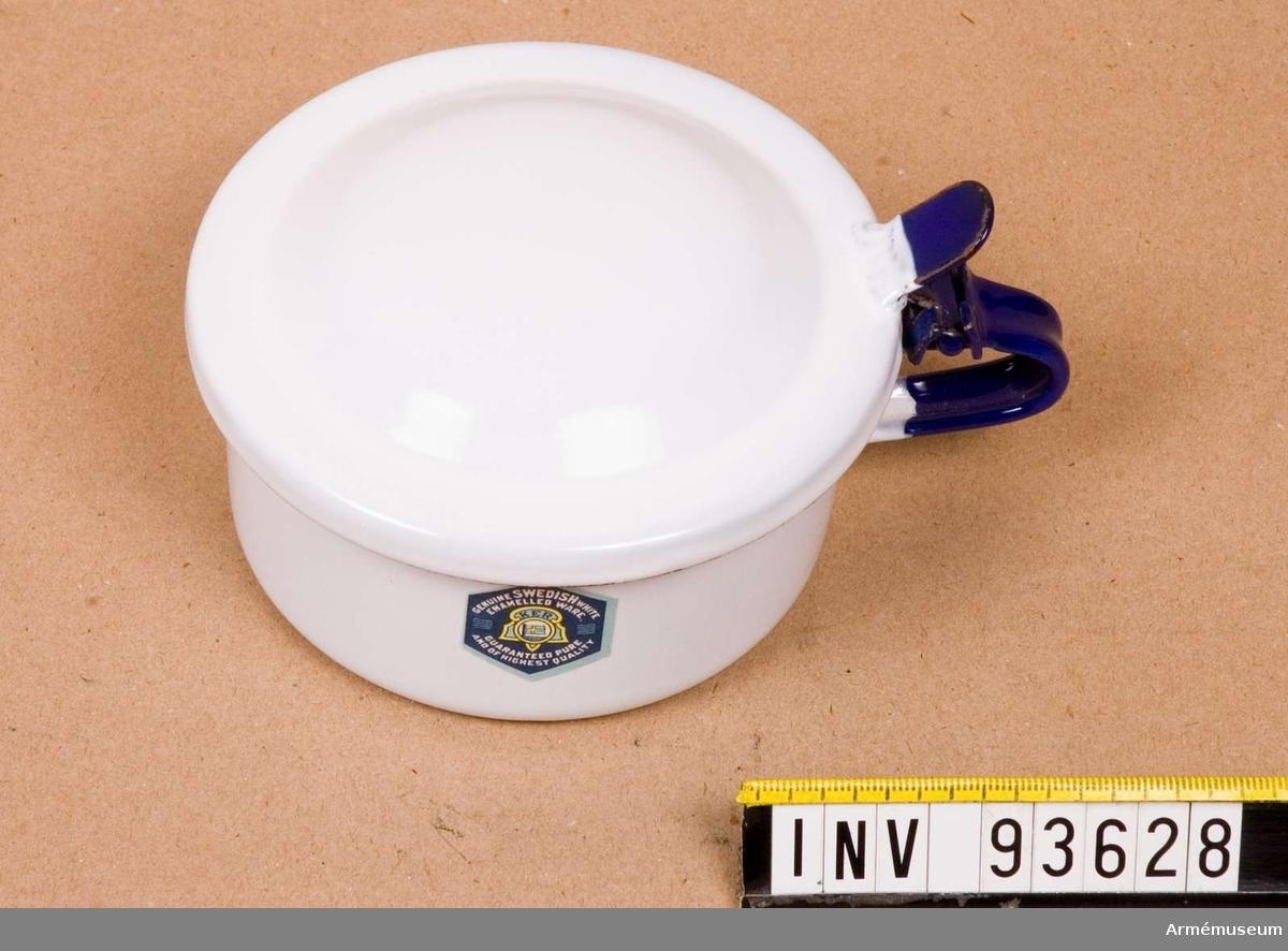 Emaljerad spotkopp med lock. Koppen och locket i vitt och handtaget i blått. Märkt med tillverkarens logotyp.