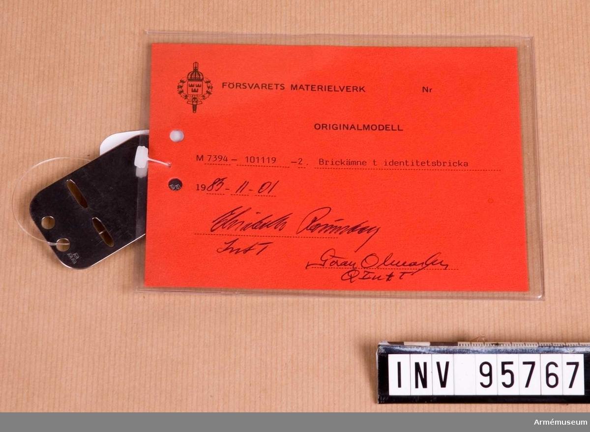 """Vidhängande etikett: """"Försvarets materielverk Originalmodell M 7394-101119-2, Brickämne till identitetsbricka, 1985-11-01 Elisabeth Rönnberg Int T / Göran Olmarker Q Int T""""."""