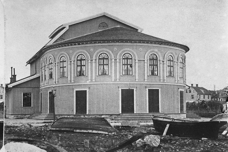 """Enligt tidigare noteringar: """"Uddevalla teater, exteriör. I förgrunden roddbåtar på land."""""""