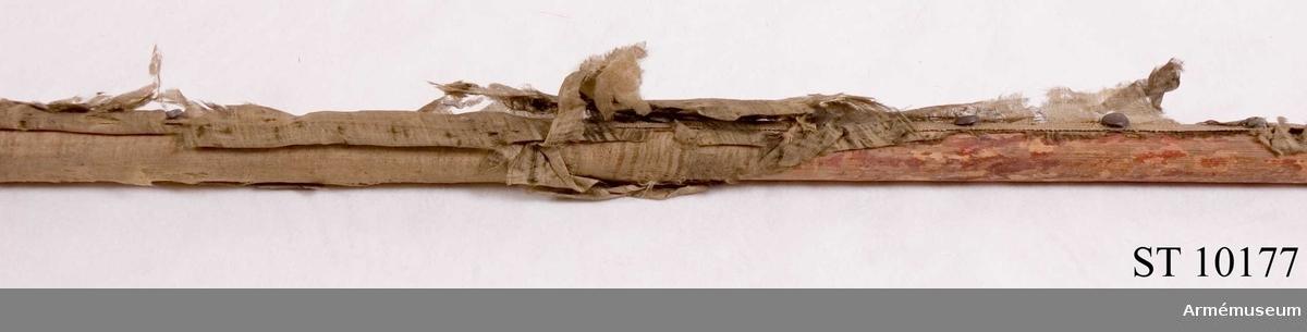 Rödmålat lövträ. Gult tännlikeband, fragment av gulgrön sidentaft.