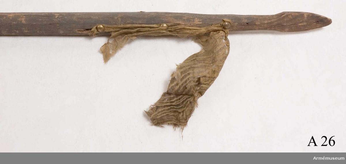 Stång av furu. Spetsen snidad i pilform. Rest av fanduk.