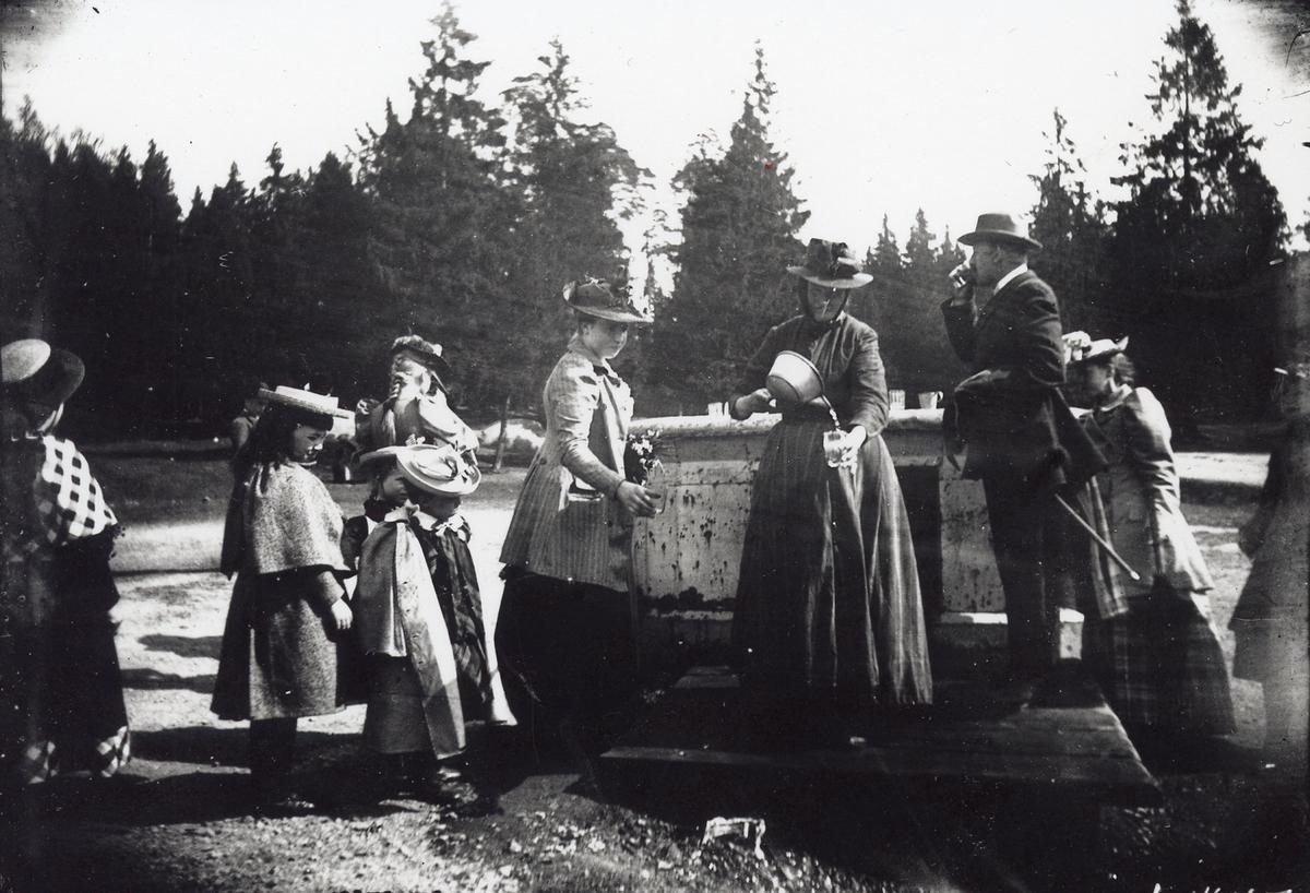 Herre, tre damer och några flickor dricker vatten vid en brunn. Se även E 001476.