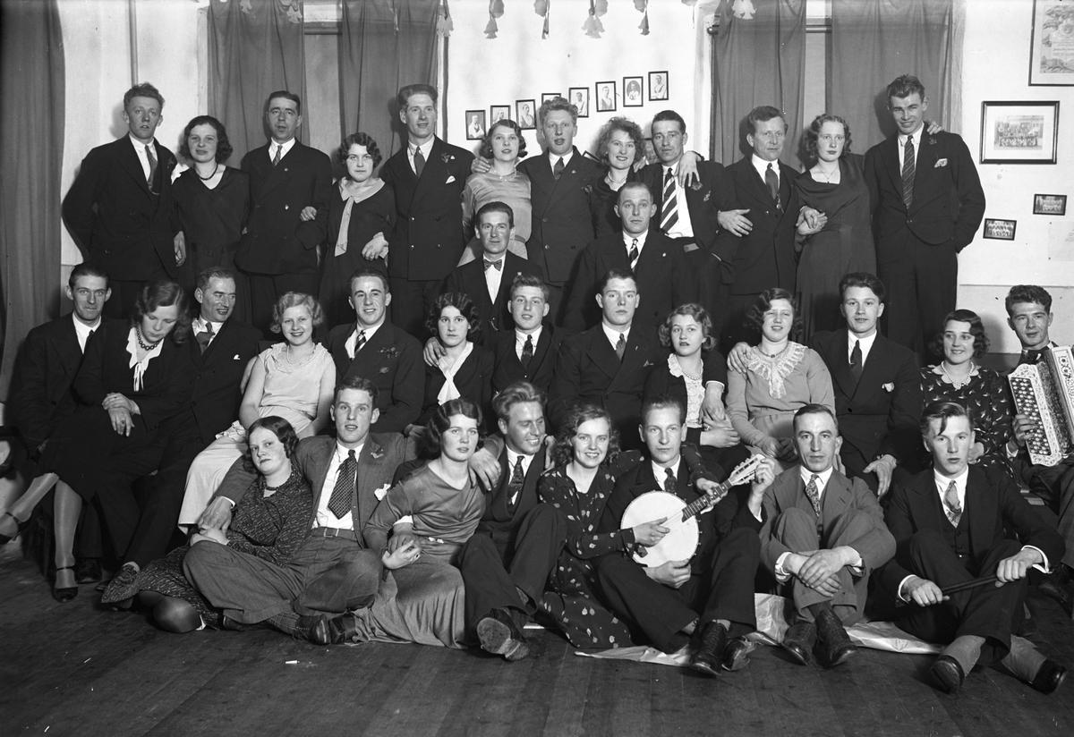 En gruppbild på unga män och kvinnor i en samlingslokal.