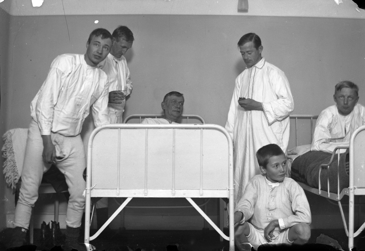 """Fem män och en pojke, alla klädda i nattskjortor eller underkäder, vid två sjukhussängar. Fotografens anmärkning: """" Blixt 10:an"""". Lungkliniken, Eksjö."""