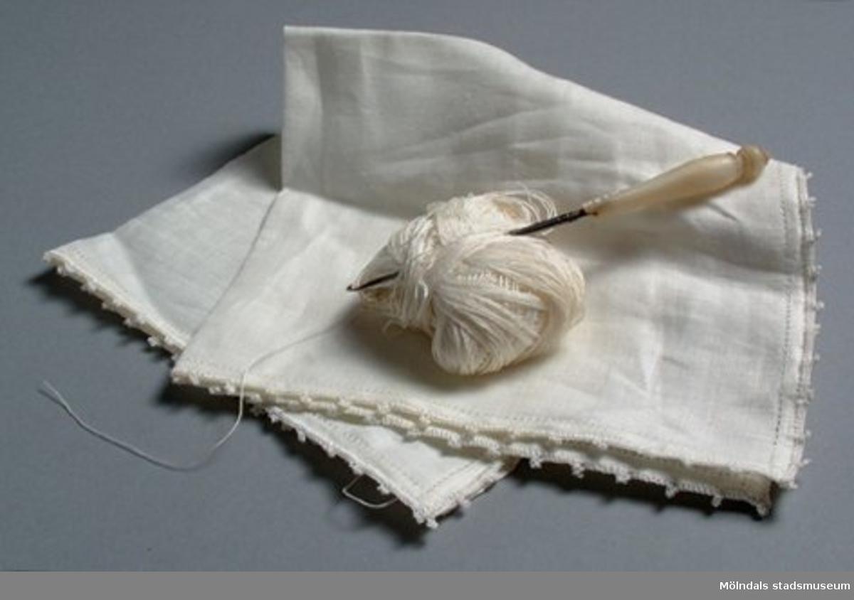 Vit linnenäsduk med ej färdigvirkad kant. Tillhörande silkesgarn uppvirat på papp och virknål med pärlemorskaft. På skaftet har en bit fallit bort.