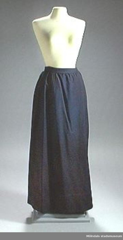 Mörkblå kjol med linning och knäppning i sidan med hank och hyska. Bred fåll med rester kvar av fem sydda sömmar. Trådrester och mörkare oblekt parti.
