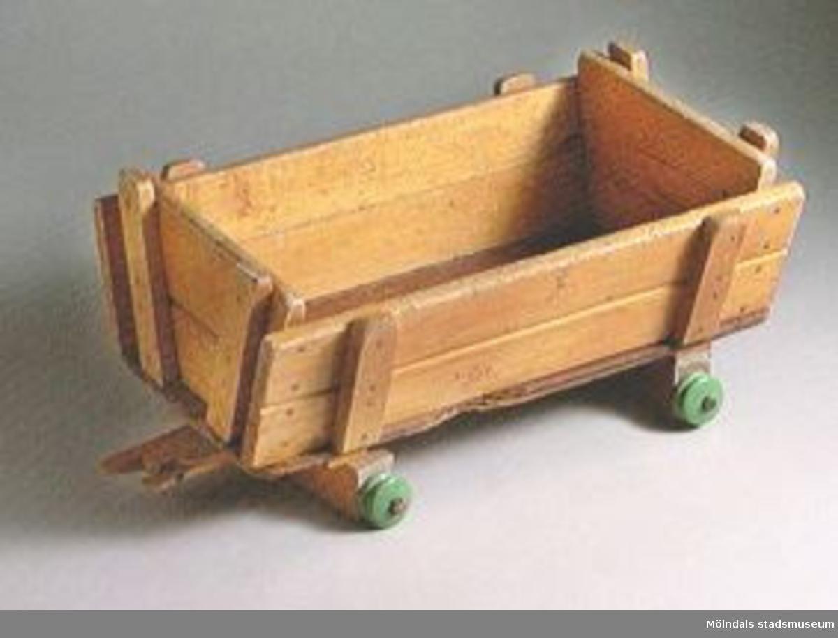 Vagn med fyra hjul, gummi saknas på tre hjul, dragstången saknas. Dragstångsfästet är trasigt.Ingår i Holtermanska samlingen.