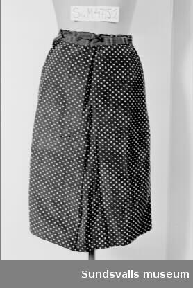 Dräkt, jacka och kjol i konstfibermaterial, svart med vita prickar. SuM 4715:1 jacka är 51 cm lång. Den har nedvikt krage och knäppning mitt fram med fyra klädda knappar. Figursydd och veck vid midjan för vidd runt höfterna. Ärm med uppvikt manschett. SuM 4715:2 kjol är 70 cm lång. Rak modell. Midjan är kantad med ett svart band fastsytt mot kjolens insida. Dragkedja i ena sidosömmen, samt metallspänne att knäppa med på insidan av dragkedjan.