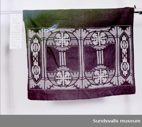 Inredningstextil i blågrön ylle, broderad och fodrad. Vidhängande lapp med texten: 'Märta Moberg'.