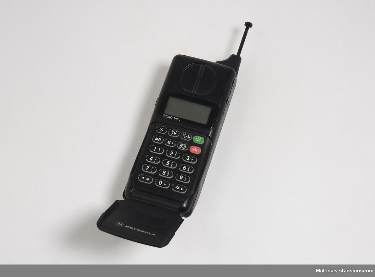 Mobiltelefon av svart hårdplast. Skyddande lucka över knapp-satsen. Display märkt Micro T-A-C. Vid användning kunde brukaren röra sig fritt med telefonen inom ett begränsat område.
