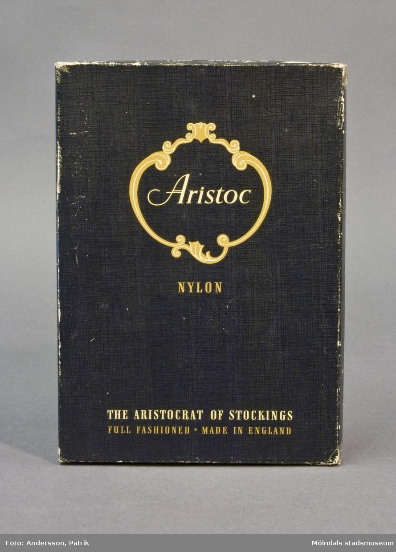 """Kartong av papp med lock. Svart med linnepräglad yta. Text i vitt och guld: """"Aristoc Nylon, The Aristocrat of Stockings, Full Fashioned, Made in England"""". Kartongen har använts för förvaring av klippdockor."""