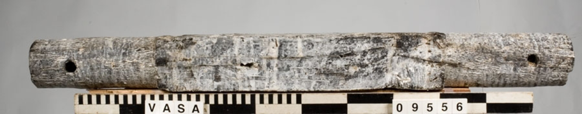 Framaxel till lavett. Ett avlångt trästycke med kvadratiskt tvärsnitt mitt på samt cylinderformade ändar. Axeln var fastsatt i lavettbottnens undersida med två grova spikar och två järnband. Bultrester kvar i ena bulthålet.