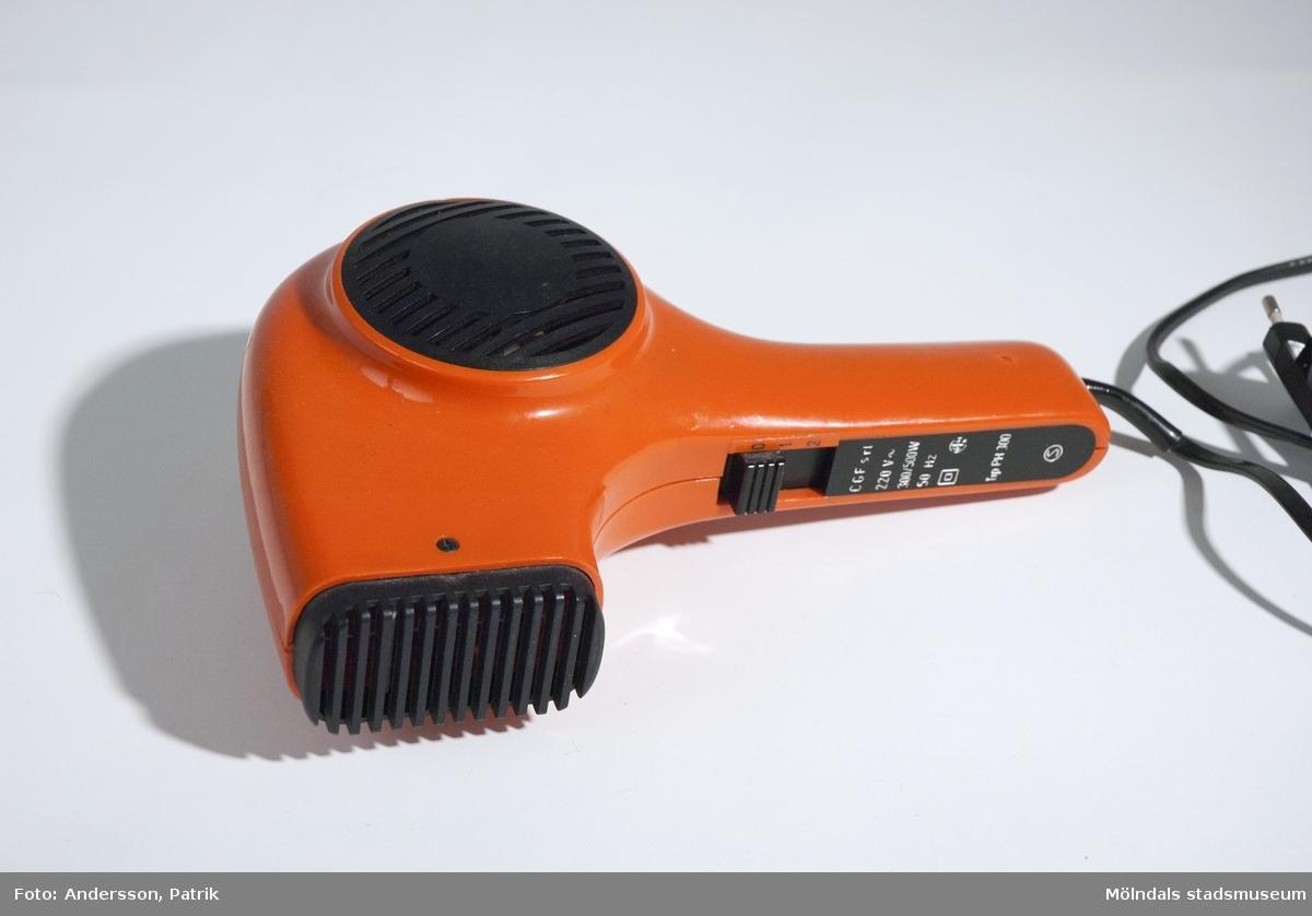 """Orange hårtork med svart sladd från 1970-talet. Det finns 2st hastigheter på den. Vid handtaget finns också dessa beteckningar tryckt: """"CGF srl220 V...300/500W50 Hz...Tip HP 300...""""MåttLängd: ca. 230 mm, Bredd: ca. 169 mm, Sladd: 1381 mm."""
