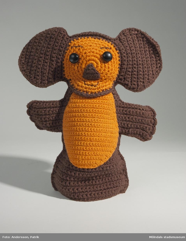 """Drutten som handdocka. Drutten var en av figuerna i barnprogrammet """"Drutten och Gena"""" som sändes på SVT mellan 1973 - 1988.Givaren virkade dockan till sin son Jonas som är född 1970. Dockan är brun med svart bakhuvud och orange ansikte och mage. Den har också trekantig brun näsa och svarta knappar som ögon.MåttLängd:277 mm, Bredd: 153 mm (med öron: 237 mm), (med armar: 226 mm)Drutten och Gena är i Sverige mest känd som en dockserie på SVT, som började sändas i Sveriges magasin den 1 september 1973. Sista avsnittet var ett specialinslag som sändes 1988.De två figurerna härstammade från Sovjetunionen och skapades av författaren Eduard Uspenskij, i barnboken Krokodilen Gena och hans vänner som utkom 1966. Gena bodde i en djurpark och fick tanken  att bygga ett Vänskapens hus, där alla ensamma djur kunde få bo. Strax mötte han Drutten, ett litet djur med dåligt självförtroende, av en art ingen någonsin hade sett förut. Barnboken blev mycket populär, kanske för att den innehöll en dold satir över sovjetsamhället, och gjordes strax om till både dockteater och dockfilm på tv.SR köpte två dockor från den sovjetiska televisionen och byggde upp ett eget programformat kring dem i Sveriges magasin, Drutten och krokodilen i bokhyllan. De svenska rösterna gjordes av Agneta Bolme Börjefors och Sten Carlberg.Sten Carlberg skrev också musiken, sångtexterna och alla manus. Han byggde ganska lite på innehållet i de ryska böckerna och filmerna och odlade sin egen speciella humor. Den ryska seriens grundtanke om kollektiv gemenskap och diskreta samhällssatir ersattes snarast av en mild satir över könsroller, till exempel den manlige besserwissern Gena försökte alltid undervisa den kvinnliga och barnsliga Drutten, som ändå till slut visade sig vara både klokare och modigare än han."""