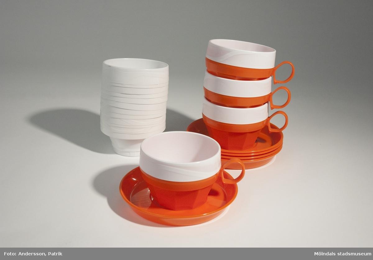 """Orange picknick servis i plast, troligtvis från 1970-talet.MM04864:1, 4 st kaffemuggshållare med fat (+ 1 st extra fat). Kaffemuggshållaren har ett """"öra"""" som handtag och har ett hål i botten. I botten, under kaffemuggshållaren finns texten: """"Meny Combi 394 Design Reg. C.A. Breger"""", gjuten i plasten. I botten, under fatet finns texten: """"FORM&IDE jONAS FORSE GNISTA"""", gjuten i plasten.Kaffemuggshållaren och fatet ingår förmodligen inte i samma serie. Mått -  Höjd: 65 mm,  Diam: ca. 90 mm (kaffemuggshållaren) Mått - Höjd: 17 mm, Diam: 135 mm (fatet) MM04864:2, 16 st engångsmuggar i vit plast som används till kaffemuggshållarna (MM04864:1). 4 st av engångsmuggarna sitter i kaffemuggshållarna.(MM04864:1).Mått - Höjd: 53 mm, Diam: ca. 90 mm Denna picknick servis kommer från en garagestädning i Balltorp 2008. En beskrivning av servisen finns på etikett som tillhört förpackning av muggarna."""